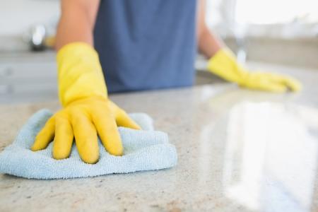 femme nettoyage: Femme nettoyant le comptoir dans la cuisine Banque d'images
