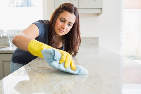 Concentrated woman scrubbing the bar in kitchen photo