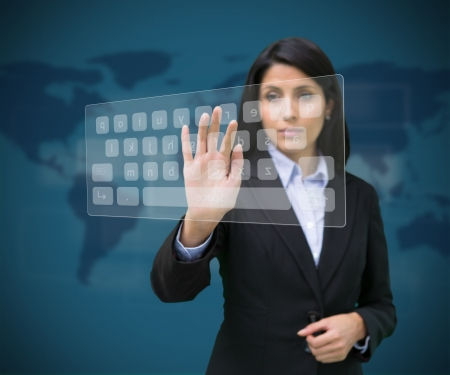 Woman touching digital keyboard against blue background with world map photo