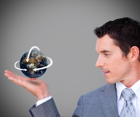 Hovering globe in businessmans hand on grey background photo
