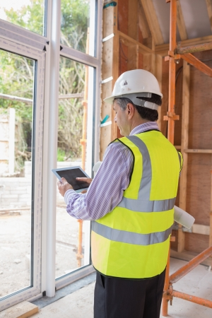 Man planning construction with the tablet pc while standing in the house photo