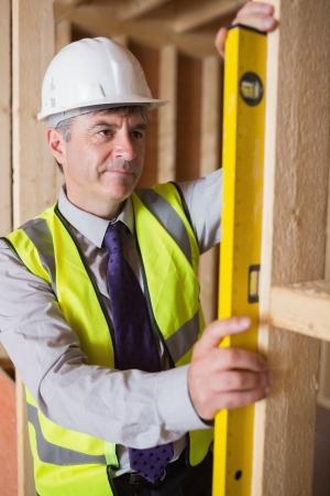 warning vest: Man with warning vest and helmet measuring wooden frame with spirit level