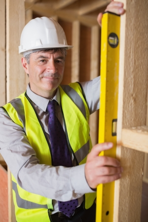 Man checking wooden frame with spirit level in construction site Stock Photo - 15584376