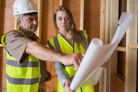 Two architects checking blueprints in consttuction site Stock Photo - 15584128