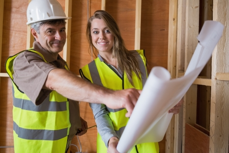 Two architects smiling with blueprints on construction site photo