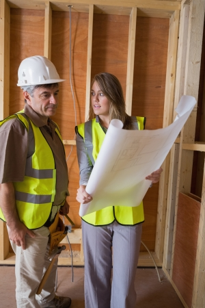 Woman and man discussing blueprints in construcion site Stock Photo - 15584123