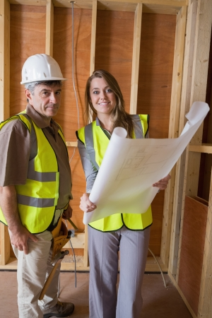 Smiling architects holding blueprints in construction site Stock Photo - 15584125