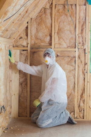 Worker in safety gear insulating walls  photo