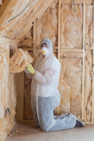 Worker filling walls with insulation in construction site photo