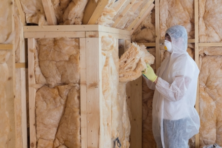 Worker filling walls with insulation material in construction site photo