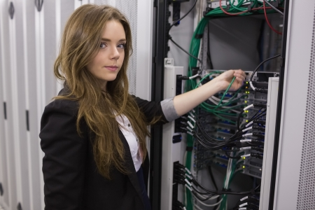 Girl working on mounted rack servers in data storage facility photo