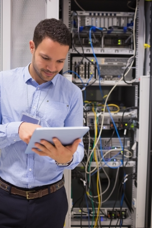 Man in data centre using a  tablet pc  photo