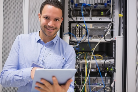 repairman: Happy worker with tablet pc in data centre Stock Photo