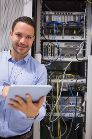 Man with tablet pc working in data centre photo