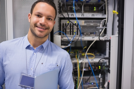 Man smiling and standing in front of data servers photo
