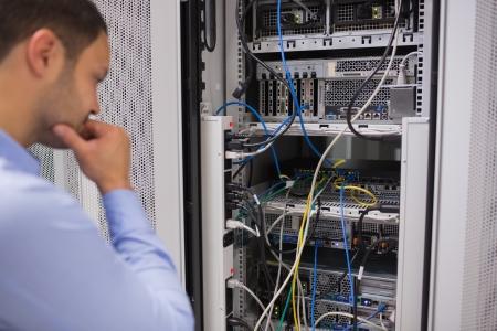 communication occupation: Uomo che guarda montato su rack server nei data center