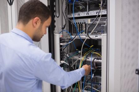 technicians: Man adjusting servers in data center