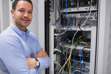 drives in information: Man with crossed arms in front of server in data centre