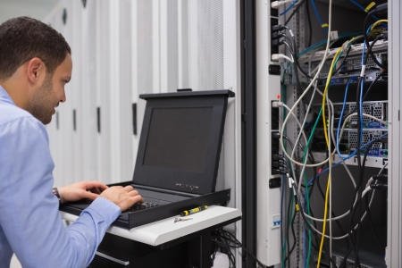 Man working with servers in data center photo