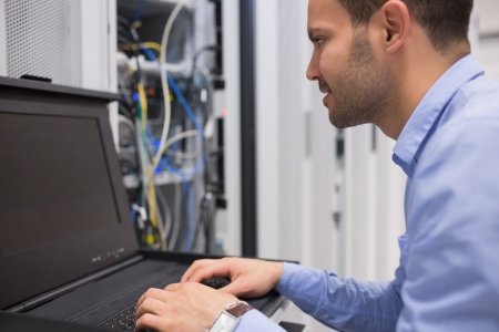 network connection plug: Man repairing servers in data center