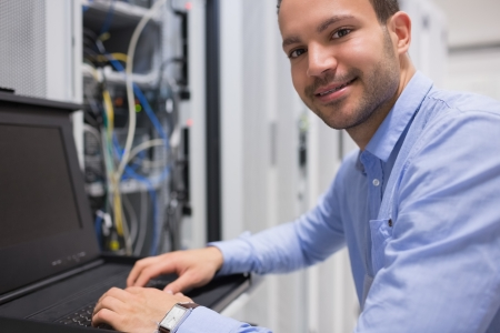 computer operator: Man searching through servers in data center