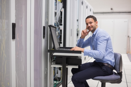 Smiling man looking up from working with servers in data center Stock Photo - 15585008