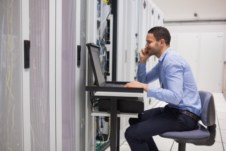 computer cable: Man maintaining the servers in data center