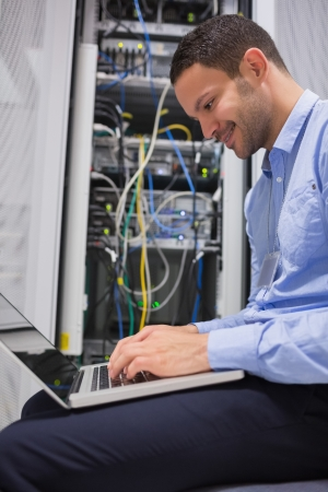 Man using laptop in front of servers in data center Stock Photo - 15593398