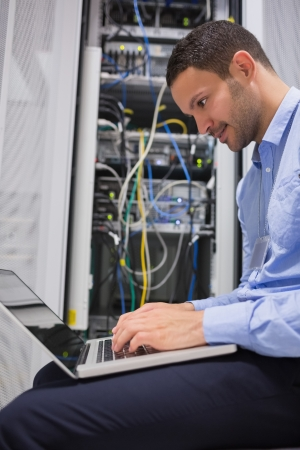 drives in information: Man using laptop beside servers in data center