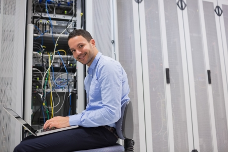 Smiling man working on the servers in data center photo