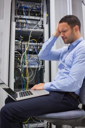 Travailleur a souligné un air avec un ordinateur portable dans des centres de données Banque d'images