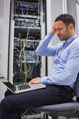 Worker looking stressed with laptop in data center photo