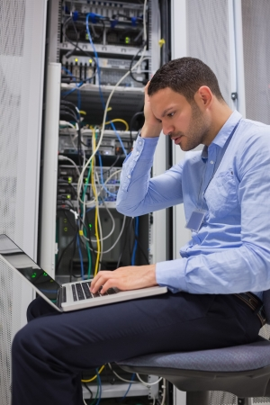 Data technician getting stressed over servers with laptop photo