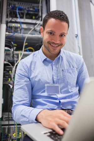 Smiling man working on servers with laptop in data center photo