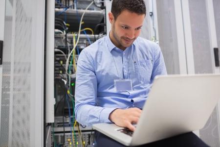 Cable network: El hombre usando la computadora port�til para comprobar los servidores del centro de datos