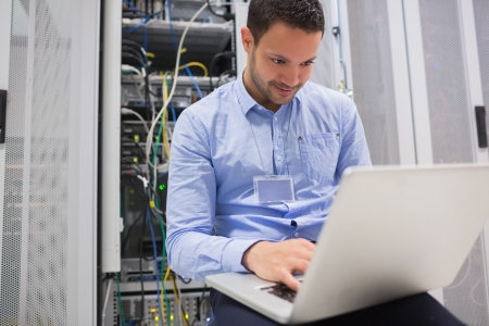 computer cable: Man using laptop to check servers in data center Stock Photo