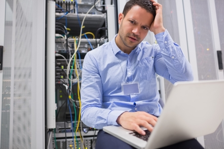Technician getting frustrated with laptop over servers in data center photo