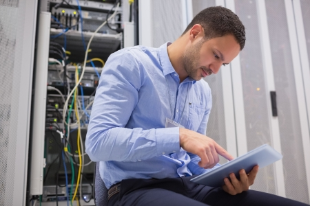server technology: Man using tablet pc beside servers in data center Stock Photo
