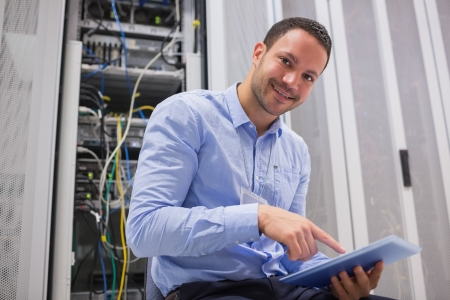 Happy technician working on tablet pc beside servers in data center photo