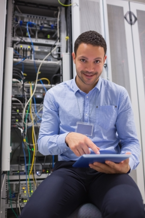 Technician working on tablet pc beside servers in data center photo