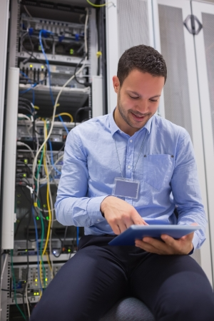 technician: Technician using tablet pc to work on servers in data center