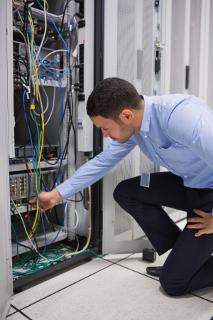 plugging: Man plugging a cable into server in data center