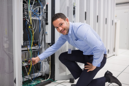 Technician plugging cable into server in data center photo