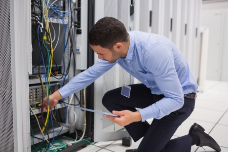 Man checking tablet pc as he is plugging cables into server in data center photo