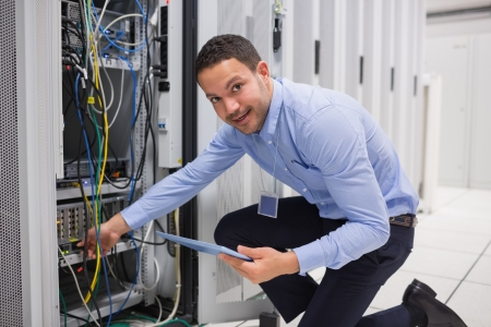 Smiling technician with tablet pc plugging cables into server in data center photo