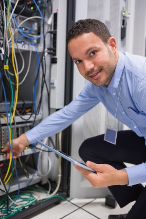 Technician plugging in cables and using tablet pc in data center photo