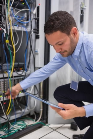 Man using tablet pc to work on servers in data center photo