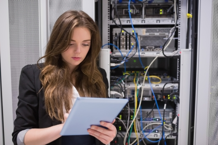 Woman using tablet pc in front of servers in data center photo