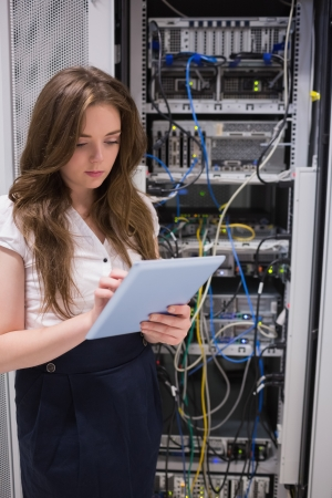 Woman checking servers using tablet pc in data center photo