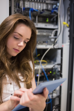 Woman working on servers checking tablet pc in data center photo